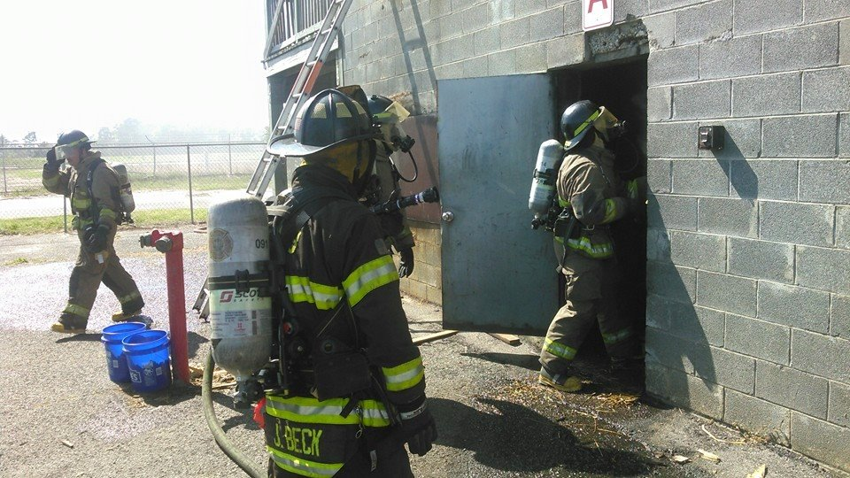 Firefighters in Gear Entering and Exiting a Building